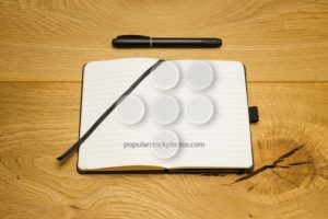 Empty pages notebook marker on desk - Popular Stock Photos
