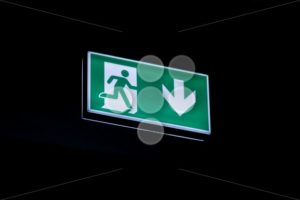 Exit sign hanging on ceiling in dark - Popular Stock Photos