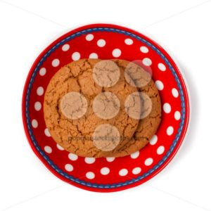 Ginger cookies on red white dotted dish isolated on white backgr - Popular Stock Photos