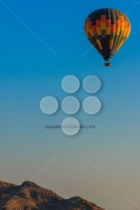 Hot air balloon floating above mountain - Popular Stock Photos
