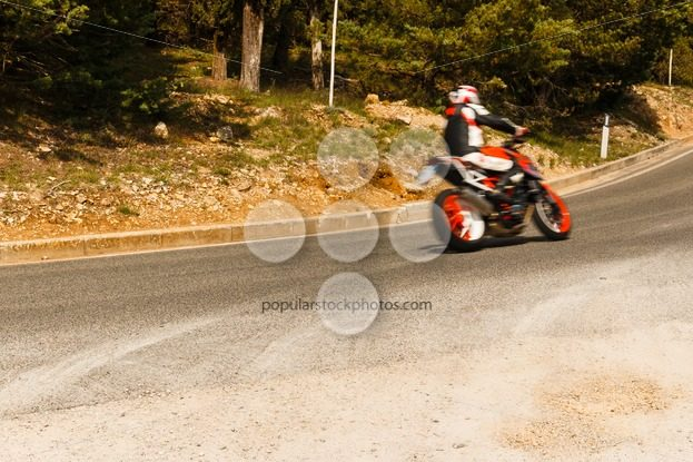 Motorbike racing corner of road - Popular Stock Photos
