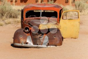 Old car wreck lying in the desert - Popular Stock Photos