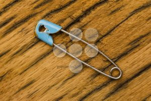 Old safety pin on wood - Popular Stock Photos