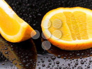 Orange fruit pieces on black surface - Popular Stock Photos