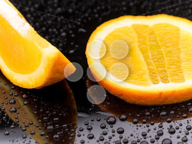 Orange fruit pieces on black surface - Popular Stock Photos