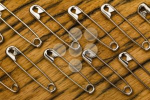 Safety pins background on wood - Popular Stock Photos