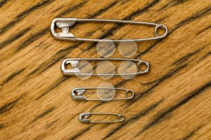 Safety pins small to big on wood - Popular Stock Photos