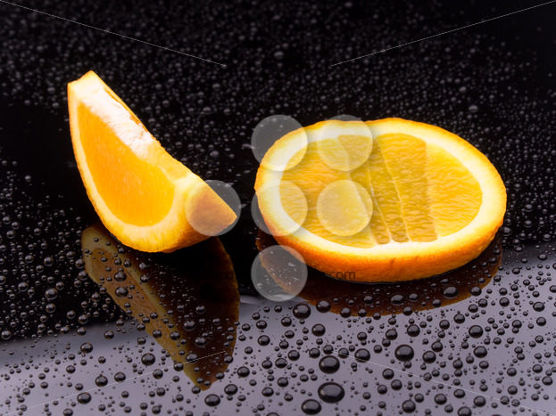Sliced orange fruit on black surface - Popular Stock Photos