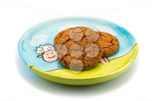 Smiling sheep underneath cookies on a colorful plate - Popular Stock Photos