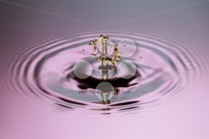 Yellow drop with mushroom close up ripples pink blue gray surfac - Popular Stock Photos