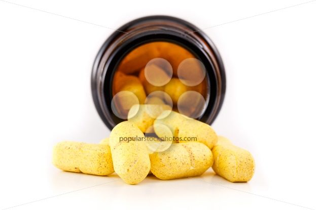 Yellow pills view inside brown bottle – Popular Stock Photos