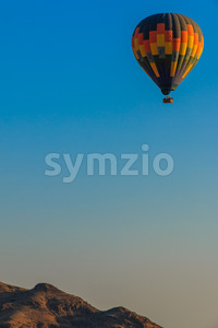 Hot air balloon floating above mountain Stock Photo