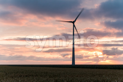 Single windmill in motion at sunset Stock Photo