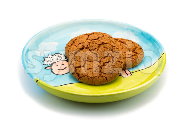 Smiling sheep underneath cookies on a colorful plate Stock Photo