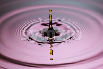 Yellow drop pillar close up ripples pink blue gray surface Stock Photo