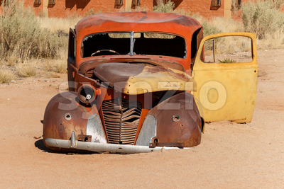 Old car wreck lying in the desert Stock Photo