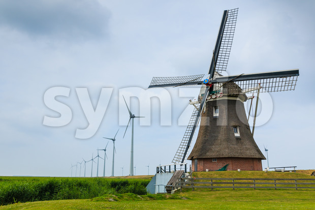 Old historic dutch windmill in the foreground and new windmills generating sustainable energy in the background. Eemshaven, Groningen, The Netherlands.