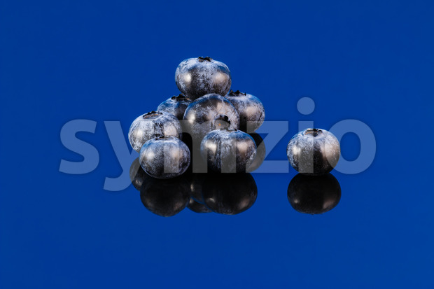 Healthy blueberries on a blue surface with reflection.