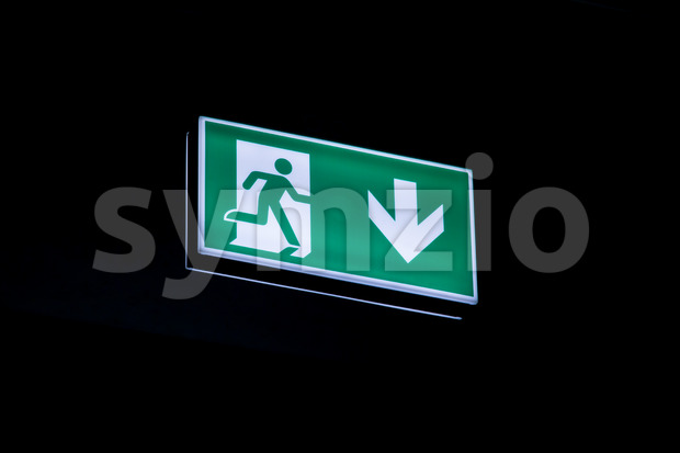 Exit sign hanging on the ceiling of a parking garage. In the dark illuminated green and white symbol.