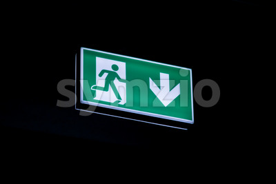 Exit sign hanging on ceiling in dark Stock Photo
