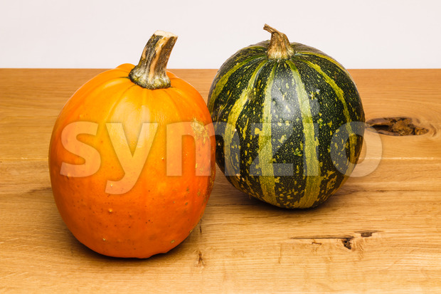 Orange and green calabash on an oak surface with white background. Autumn crop used for decoration and during halloween.