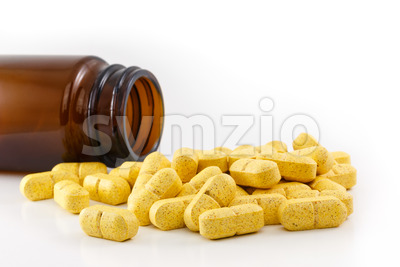 Yellow pills emptied bottle Stock Photo