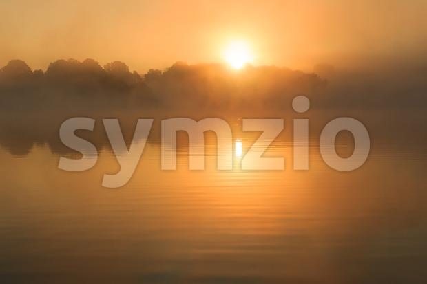 Orange sun rising over lake France Stock Photo
