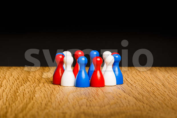 Concept for teamwork. Red white blue pawn figures and black background on wooden surface. National three colors of flag Croatia, ...