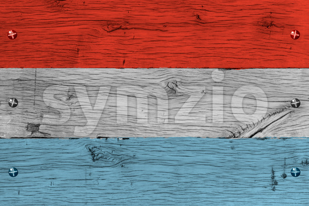 Grand Duchy of Luxembourg national flag. Painting is colorful on wood of old train carriage. Fastened by screws or bolts.