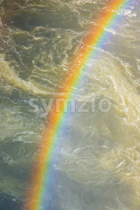 Rainbow over fast flowing river Stock Photo