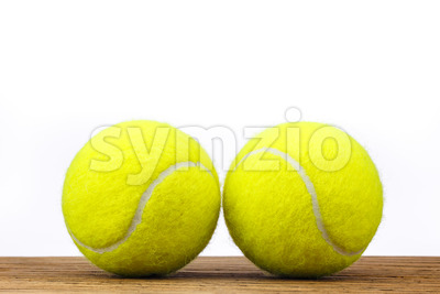 Two tennis balls table wood isolated Stock Photo