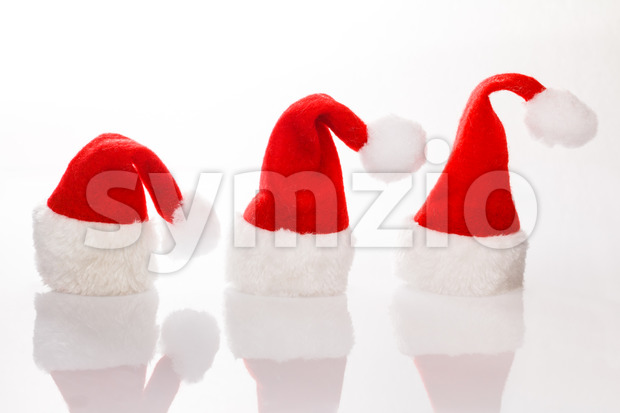 Three hats Santa in a row for Christmas. Isolated on white background with reflection. Room for text, copy space.