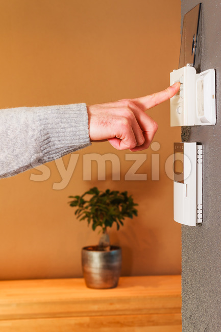 Young male hand pressing button of electronic appliance on wall of modern home. Clean background scene gray wool sweater.