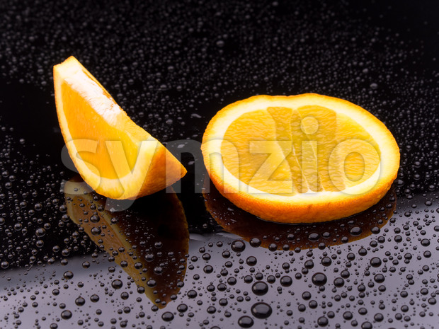 Sliced orange fruit on black surface Stock Photo