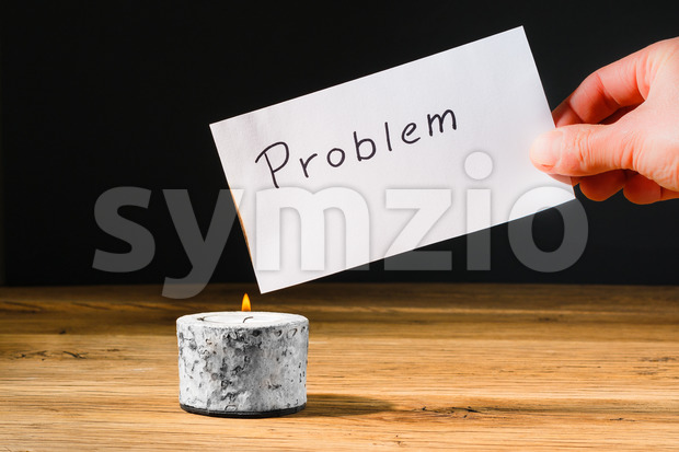 Concept for solving or letting problem disappear by burning paper with text problem