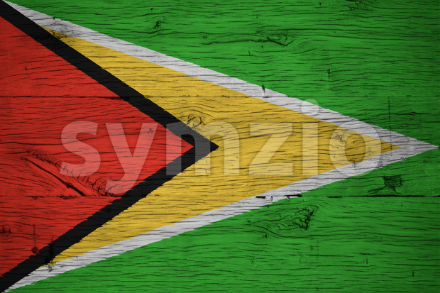 Guyana national flag painted on old oak wood. Painting is colorful on planks of old train carriage.