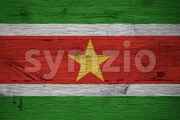 Suriname national flag painted on old oak wood. Painting is colorful on planks of old train carriage.