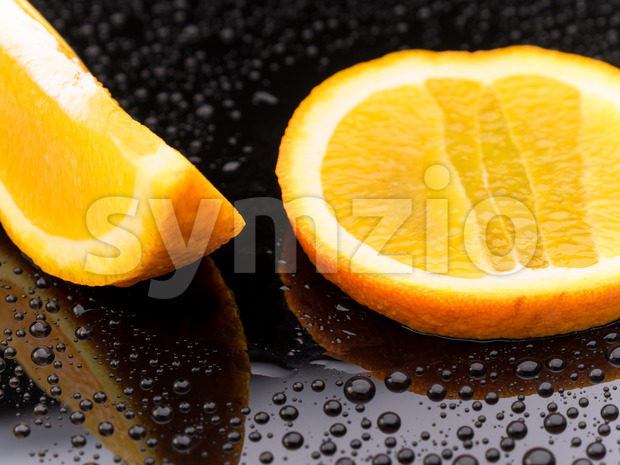 Orange fruit pieces on black surface Stock Photo