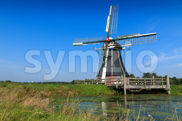 Historic windmill in water landscape. Windmill De Helper near Haren in Groningen, The Netherlands.