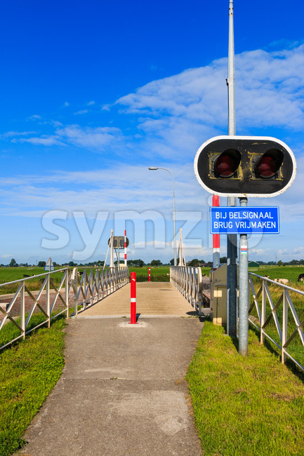 Bycicle bridge crossing Reitdiep river in Groningen, the Netherlands. With warning sign and lights.