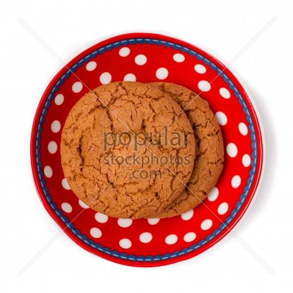 Ginger cookies on red white dotted dish isolated on white backgr