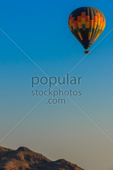 Hot air balloon floating above mountain