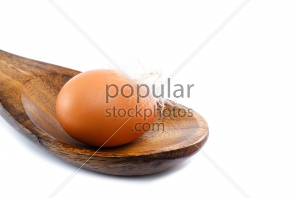 Close up egg with feather spoon
