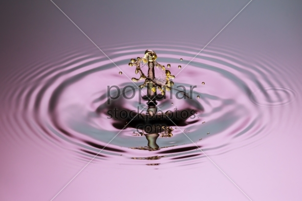 Yellow drop with mushroom close up ripples pink blue gray surfac