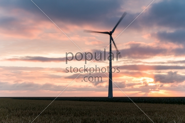 Single windmill in motion at sunset