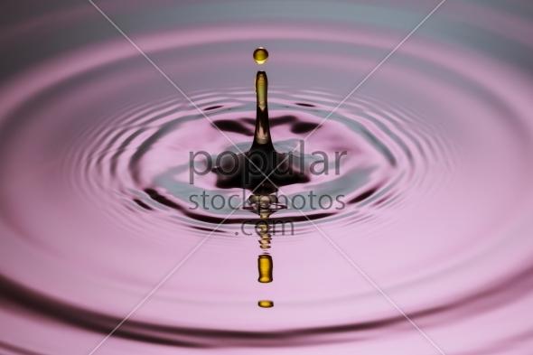 Yellow drop pillar close up ripples pink blue gray surface